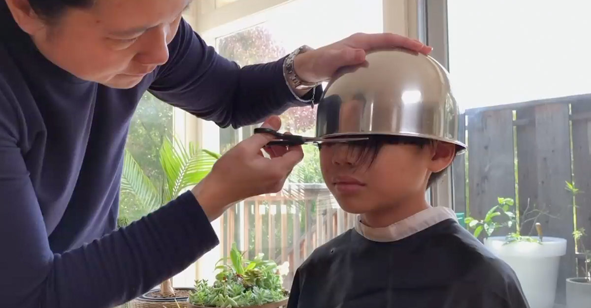 Image of a boy having a bowl haircut by his father