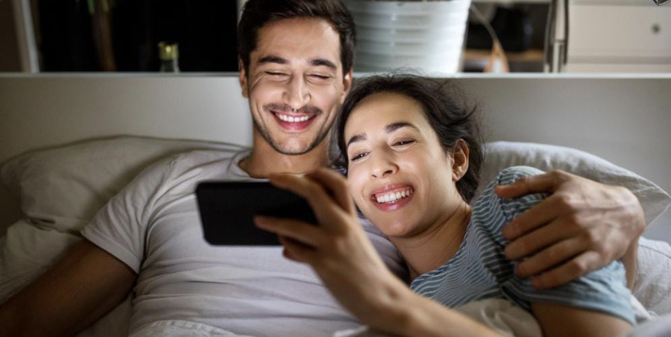 Two people at home watching video together on a phone