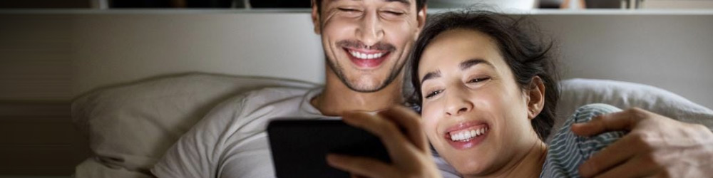 Couple at home watching TV on a phone